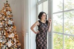 Mujer joven cerca de un árbol de navidad Fotos de archivo libres de regalías