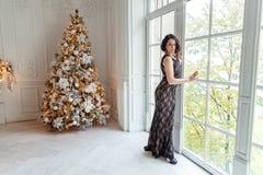 Mujer joven cerca de un árbol de navidad Fotos de archivo