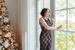 Mujer joven cerca de un árbol de navidad Imagen de archivo libre de regalías