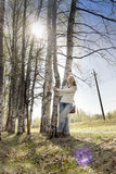 Mujer joven cerca de un abedul en parque en la primavera temprana Imagen de archivo