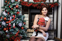 Mujer joven cerca del árbol de navidad y de la chimenea Imagen de archivo