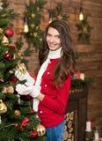 Mujer joven cerca del árbol de navidad y de los regalos el víspera del ` s del Año Nuevo Imagenes de archivo