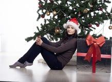 Mujer joven cerca del árbol del Año Nuevo con el presente Foto de archivo libre de regalías