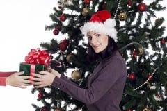 Mujer joven cerca del árbol del Año Nuevo con el presente Imagen de archivo libre de regalías