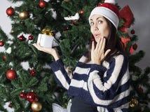 Mujer joven cerca del árbol del Año Nuevo con el presente Imagen de archivo
