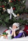 Mujer joven cerca del árbol del Año Nuevo con el presente Imágenes de archivo libres de regalías