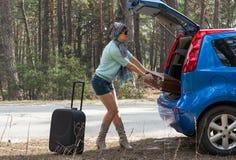 Mujer joven cerca del coche con una maleta en el camino Foto de archivo