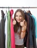Mujer joven cerca del estante con las suspensiones imágenes de archivo libres de regalías