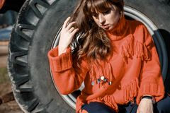 Mujer joven cerca del maíz muchacha hermosa en el pueblo muchacha cerca de un tractor rojo Maquinaria agrícola imagen de archivo
