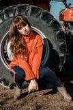 Mujer joven cerca del maíz muchacha hermosa en el pueblo muchacha cerca de un tractor rojo Maquinaria agrícola imágenes de archivo libres de regalías