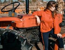 Mujer joven cerca del maíz muchacha hermosa en el pueblo muchacha cerca de un tractor rojo Maquinaria agrícola foto de archivo