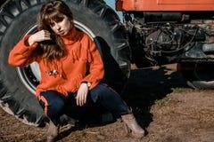 Mujer joven cerca del maíz muchacha hermosa en el pueblo muchacha cerca de un tractor rojo Maquinaria agrícola imagenes de archivo