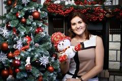 Mujer joven cerca del árbol de navidad y del muñeco de nieve Fotografía de archivo