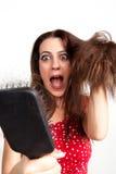 Mujer joven chocada con el cepillo de pelo fotografía de archivo libre de regalías