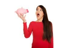 Mujer joven chocada con el piggybank Fotos de archivo libres de regalías
