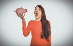 Mujer joven chocada con el piggybank Foto de archivo libre de regalías