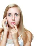 Mujer joven chocada con el teléfono celular Imagen de archivo
