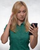 Mujer joven chocada en camisa verde casual con el smartphone a disposición que mira el teléfono foto de archivo