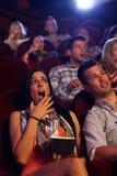 Mujer joven chocada en el cine Fotos de archivo
