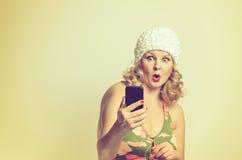 Mujer joven chocada que mira fijamente su móvil Imágenes de archivo libres de regalías