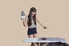 Mujer joven chocada que mira la camisa quemada en el tablero que plancha sobre fondo coloreado Imagen de archivo