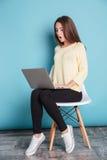 Mujer joven chocada que mira la pantalla del ordenador portátil Imagen de archivo