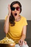 Mujer joven chocada que mira la película 3D Fotos de archivo libres de regalías