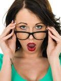 Mujer joven chocada que mira sobre sus vidrios con su boca abierta Fotografía de archivo
