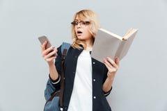 Mujer joven chocada que usa el teléfono y sosteniendo el libro Imagen de archivo libre de regalías