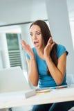 Mujer joven chocada que usa un ordenador portátil Fotografía de archivo