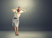 Mujer joven chocada sobre oscuridad Imagen de archivo libre de regalías