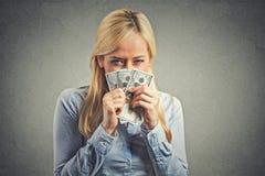 Mujer joven codiciosa, sosteniendo billetes de banco apretados del dólar Imagen de archivo