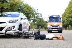 Mujer joven con accidente de la bicicleta y el coche de la ambulancia que viene Fotos de archivo libres de regalías