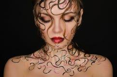 Mujer joven con arte mojado del pelo y de la cara Foto de archivo libre de regalías
