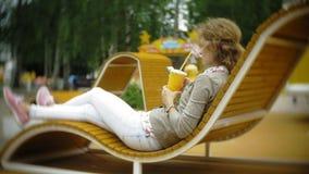 Mujer joven con batido de leche y el teléfono celular al aire libre en un banco creativo cómodo almacen de video