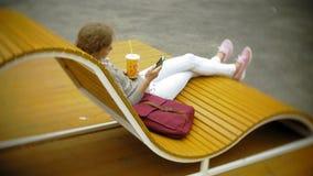 Mujer joven con batido de leche y el teléfono celular al aire libre en un banco creativo cómodo metrajes