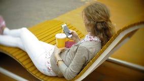 Mujer joven con batido de leche y el teléfono celular al aire libre en un banco creativo cómodo almacen de metraje de vídeo
