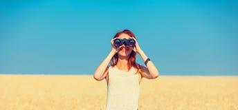 Mujer joven con binocular Fotos de archivo libres de regalías