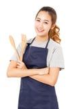 Mujer joven con cocinar las herramientas que llevan el delantal Imagen de archivo libre de regalías