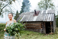 Mujer joven con con la escoba de abedul fresca y baño de calefacción en fondo Fotografía de archivo libre de regalías