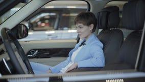 Mujer joven con corte de pelo corto en el traje azul del desgaste formal que se sienta dentro de un coche en asiento delantero de almacen de metraje de vídeo