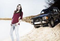 Mujer joven con del coche del camino en la duna de arena Foto de archivo