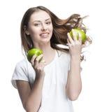 Mujer joven con dos manzanas verdes Fotos de archivo
