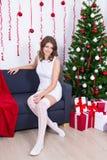 Mujer joven con el árbol de navidad adornado en casa Fotografía de archivo libre de regalías