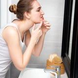 Mujer joven con el acné que exprime sus puntos con el espejo del cuarto de baño Fotos de archivo