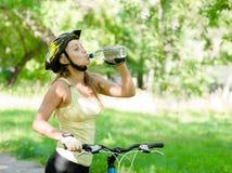 Mujer joven con el agua potable de la bici de montaña Imagen de archivo