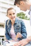 Mujer joven con el amigo masculino que estudia junto en el campus de la universidad Imagen de archivo libre de regalías