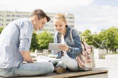 Mujer joven con el amigo masculino que usa la tableta digital en el campus de la universidad Imágenes de archivo libres de regalías