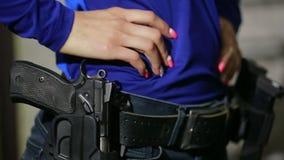 Mujer joven con el arma en una radio de tiro interior recoja el arma almacen de metraje de vídeo