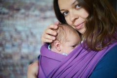 Mujer joven con el bebé del niño recién nacido en una honda fotografía de archivo